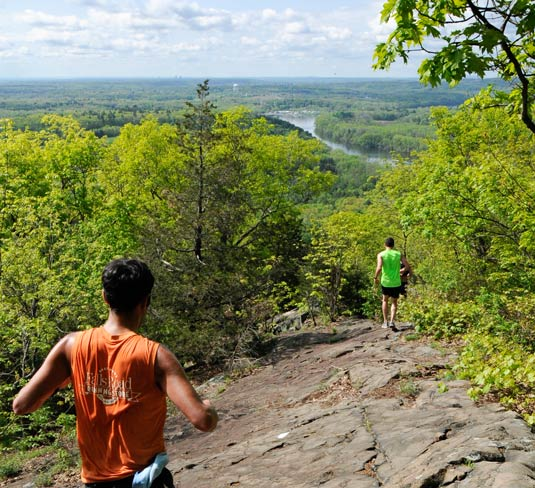 Runners along a rocky ridge trail overlooking Connecticut River.
